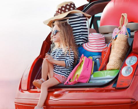 Frau sitzt mit Taschen im offenen Kofferraum